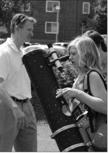 Dr. Steve Maier helps students view the eclipse through a telescope.
